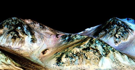 Ove tamne, uske, 100 metara duge pruge prostiru se niz padine na Marsu, i zaključeno je da su formirane od strane tečne vodu. Nedavno, naučnici su detektovali hidrate soli na padinama kratera Hale. Ovo otkriće ide u prilog prvobitnoj hipotezi da je pruge zaista formirala tečna vode. Plava boja koja se može videti nije u vezi sa njihovom nastanku, već potiče od prisustva minerala piroksena. (Credit: NASA/JPL/University of Arizona)